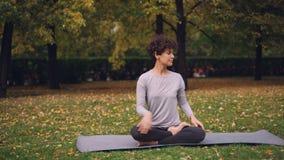 Het slanke meisje doet yogaoefeningen voor gezond stekel het uitrekken zich lichaam en bewapent dan het ontspannen in lotusbloemp stock footage