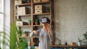Het slanke meisje gebruikt virtuele werkelijkheidsglazen die zich thuis in de ruimte bevinden van de zolderstijl en het bewegen z stock footage