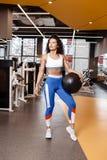 Het slanke meisje met donker krullend haar gekleed in een sportkleding bevindt zich met zware geschiktheidsbal in de moderne gymn stock foto's