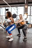 Het slanke meisje in het modieuze heldere sportenkleren doen terug hurkt met barbell en een ander atletisch meisje helpt haar in stock foto's