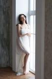 Het slanke meisje omvatte zich met een doek bij het venster Stock Fotografie