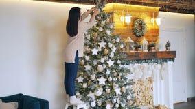 Het slanke meisje in sweater en jeans verfraait mooie Nieuwjaarboom wat betreft ballen en sterren en perfect creëren stock video