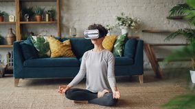 Het slanke meisje in virtuele werkelijkheidsglazen mediteert thuis zitting op vloer in lotusbloem persoonlijke positie en geniete stock videobeelden