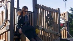 Het slanke meisje zit in park en houdt gevallen de herfstbladeren en verzamelt boeket stock footage