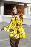 Het slanke modieuze donkerbruine meisje gekleed in geel met bruine bloemenblouse loopt in de straat op een zonnige dag stock foto