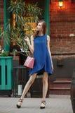 Het slanke mooie meisje gekleed in een blauwe de zomerkleding die een roze zak houden bevindt zich in een stadsstraat op een warm royalty-vrije stock fotografie