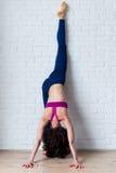Het slanke vrouw doen die zich gespleten tegen de muur bevinden De slanke vrouwelijke yogi die yoga uitvoeren stelt geroepen Urdh Stock Afbeeldingen