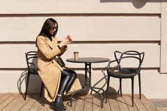 Het slanke zwarte haired wijfje zit in openlucht bij lijst die, kop van hete drank hebben, ontspannend tijdens vrije tijd, die fo royalty-vrije stock afbeeldingen