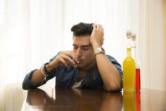 Het slaperige, gedronken jonge mensenzitting drinken alleen bij een lijst met twee flessen stock foto