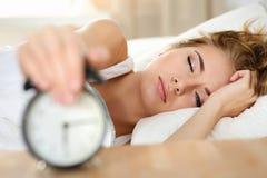 Het slaperige jonge vrouwenportret met één opende oog die dodenalar proberen royalty-vrije stock afbeeldingen