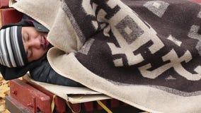 Het slechte bevroren zieke mens hoesten, die warm op bank, dakloosheid, armoede proberen te worden stock footage