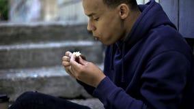 Het slechte dakloze die jongen eten blijft van voedsel op straat, wrede werkelijkheid, armoede wordt gevonden stock fotografie