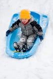 Het sledding van de jongen onderaan heuvel Royalty-vrije Stock Afbeeldingen