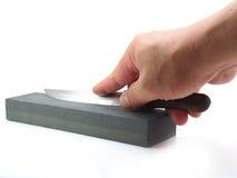 Het slijpen van een mes op wit Royalty-vrije Stock Foto