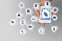 Het slimme die concept van de huisautomatisering door moderne slimme telefoon wordt geïllustreerd om slimme voorwerpen te control stock foto's