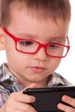 Het slimme jonge geitje speelt met slimme celtelefoon Royalty-vrije Stock Foto's