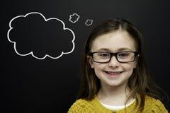 Het slimme jonge meisje bevond zich infront van een bord Stock Foto