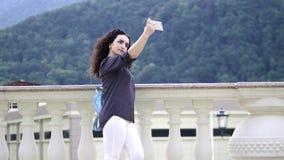 Het slimme, mooie brunette verbetert krullend haar en maakt selfie op een mobiele telefoon tegen de achtergrond van opmerkelijk stock video