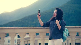 Het slimme, mooie brunette verbetert krullend haar en maakt selfie op een mobiele telefoon tegen de achtergrond van opmerkelijk stock videobeelden