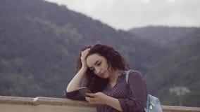 Het slimme, mooie brunette verbetert krullend haar en spreekt op de mobiele cellulaire telefoon tegen de achtergrond van stock videobeelden
