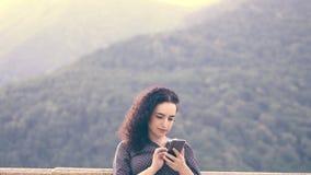 Het slimme, mooie brunette verbetert krullend haar en spreekt op de mobiele cellulaire telefoon tegen de achtergrond van stock footage