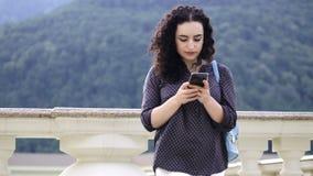 Het slimme, mooie brunette verbetert krullende haar en drukken sms op de telefoon bij tegen de achtergrond van opmerkelijk stock footage