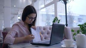 Het slimme mooie meisje tijdens e-leert op videopraatje op moderne netbook toont blocnote met nota's en glimlacht zitting bij a stock footage