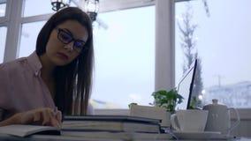 Het slimme studentenmeisje tijdens e-leert gebruiks moderne netbook met boeken en schrijft nota's in notitieboekjezitting bij lij stock video