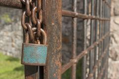Het slot op de ketting Oude roestige ketting met een slot op de ijzerpoort De symboolopsluiting en slavernij Stock Foto