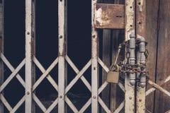 Het slot van het vooraanzicht oude gouden staal en beschadigd en geroeste staaldeur op houten deur stock fotografie