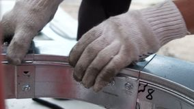Het sluiten van de close-upgeschoolde arbeider door het detailbovenkant van het handenmetaal stock footage