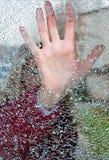 Het sluiten van het meisje overhandigt een gat in glas Stock Foto