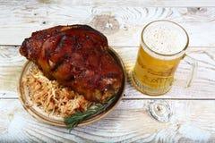 Het smakelijke Beierse gewricht van het braadstukvarkensvlees met zuurkool en een glas bier in Beiers recept Oktoberfestmenu stock afbeeldingen