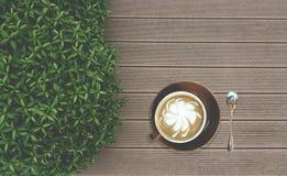 Het smakelijke die drinken, een kop van cappuccinokoffie met de melk van het bloempatroon vooruit in bruine ceramische kop wordt  stock afbeelding