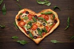 Het smakelijke Italiaanse hart vormde pizza met kip, paddestoelen en verspreidde arugula` s bladeren op houten rustieke achtergro Royalty-vrije Stock Foto's
