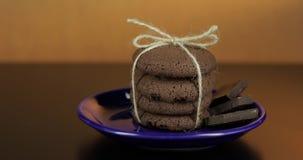 Het smakelijke kijken chocoladekoekje op een blauwe plaat op donkere oppervlakte Warme achtergrond stock videobeelden