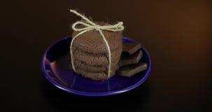 Het smakelijke kijken chocoladekoekje op een blauwe plaat op donkere oppervlakte Warme achtergrond stock video