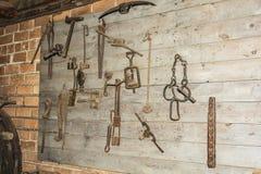 Het smeden op de houten muur in de landelijke smidse Stock Foto