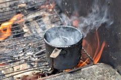 Het smelten zwarte teer in metaalkop op vuurstoom stock afbeelding