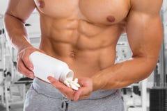 Het smeren van de anabole spieren van de de bodybuilder bodybuilding gymnastiek van het pillenmisbruik stock afbeelding