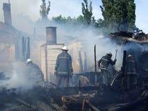 De brandbestrijders doven een brand in een flatgebouw Stock Foto
