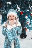 Het sneeuwmeisje in het bosmeisje bevroor over in de winter het kind verwarmt zijn handen Gelukkig Nieuwjaar royalty-vrije stock foto