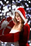 Het sneeuwmeisje in rood kostuum opent een rode gift voor Kerstmis en Nieuwjaar 2018.2019 Royalty-vrije Stock Afbeeldingen