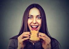 Het snelle voedsel is mijn favoriet Vrouw die een hamburger eet stock foto's