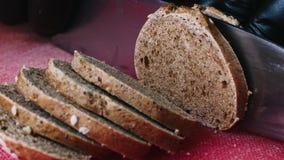 Het snijden van het broodje met sesamzaden met een keukenmes op rode raad in 4k-resolutie in slowmotion stock video