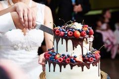 Het snijden van de huwelijkscake met bessen stock afbeeldingen