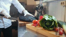 Het snijden van een brok van gerookt vlees op een houten raad stock videobeelden