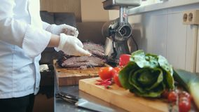 Het snijden van een brok van gerookt vlees op een houten raad stock footage