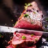 Het snijden van een gedeelte van zeldzaam braadstukrundvlees Stock Fotografie
