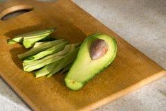 Het snijden van een rijpe fruitavocado op een keukenraad Stock Afbeelding